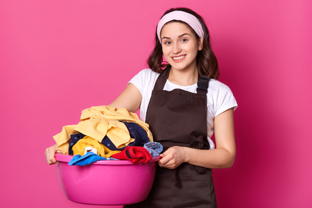 Young smiling cute female walking with pink basin, having much laundry, holding it with both hands, looks positive and sincere. Busy attractive housewife stands isolated over pink background.