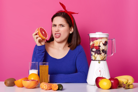 Indoor shot of disgruntled young female with bright red headband on her head, wearing dark blue sweatshirt, showing her tongue with disgust, holding grapefruit in one hand, looks upset and annoyed.