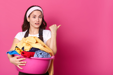 Charismatic pretty housewife standing in studio, holding pink basin with laundry with one hand, making gesture with her thumb, showing direction, looks impressed. Copy space for advertisement. 版權商用圖片