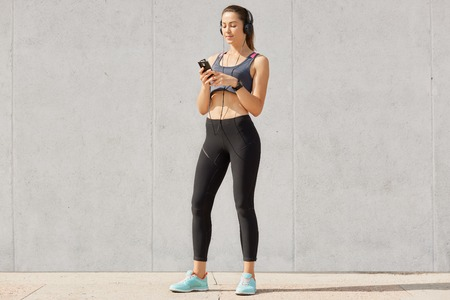 Sporty woman listening music in headphones while training in gymnasium, dressed top and legging, shows bared stomach, posing over gray studio background.
