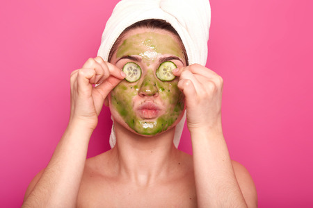 Indoor shot of young attractive woman with green mask on her face putting parts of cucumber on her eyes, protruding her lips, having naked body, wears white towel on her hair, relaxing spa time. 版權商用圖片