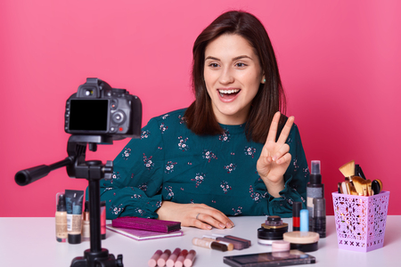 Funny cheerful blogger makes sign, rise two fingers, opens mouth widely, getting pleasure from shooting, going to tell her subscribers about cosmetics, being in high spirits. Make up concept. Stockfoto