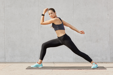 Fit and healthy woman stretches before running, Caucasian female wearing tank top, black legging and blue sneakers doing sport exercises on mat in gym, model posing alone over grey background. Stock Photo