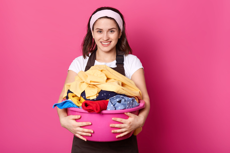 Energetic positive brunette housewife looks directly at camera, walking with pink basin with laundry, looks funny and happy. Slender charming model posing isolated over bright pink background.