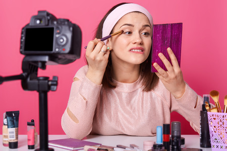 Close up portrait of young Caucasian woman blogger, advertising new eye shadow for her followers, online translation, lady looks at mirror, makes tutorial video for beauty blog.
