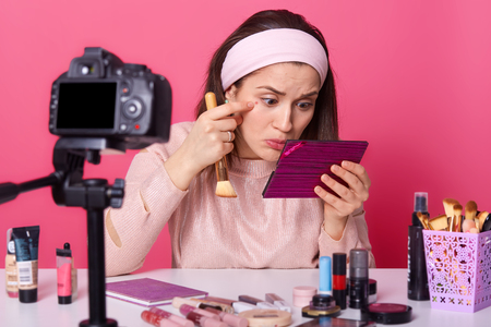 Shot of female blogger notices acne under her eyes, holds cosmetic brush and mirror, sits at camera while recording blog for website, isolated over pink background. Online translation, beauty blogging