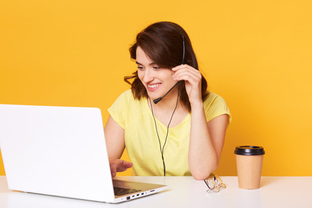 Image of brunette woman in yellow casual t shirt sits on chair at white desk and working on laptop over studio background. Stok Fotoğraf