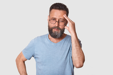 Close up portrait of handsome middle aged man. Bearded male in grey clothes and glasses thinking and looking aside, keeps hand on temple, has worried facial expression. Problem and people concept. 免版税图像