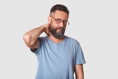 Tired unemotional handsome executive looks firmly at camera, holding his arm behind, making neck massage after hard working day. Middle aged black haired model wearing stylish specs and t shirt.