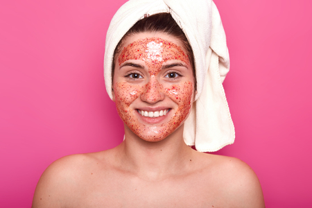 Close up portrait of smiling cheerful young woman smiling sincerely, enjoys her weekends doing spa procedures, having colorful face scrub, covering her hair with white towel. Skincare concept. Stock fotó