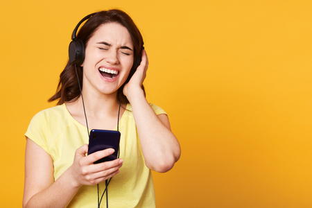 Happy carefree young woman listening to music from smartphone over studio background, singing song she likes loudly, standing with closed eyes, touches her earphones, dressed casual yellow t shirt. Stock Photo