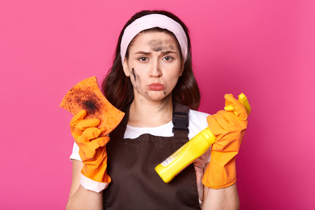 Disappointed exhausted black haired housewife has no energy to tidy up, looking directly at camera with upset facial expression, wearing white headband, brown apron and casual white t shirt.