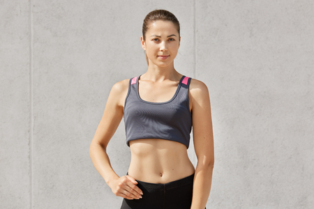 Half length shot of confident young sportswoman has slim perfect body shape, wearing sport clothes, models indoor alone isolated over gray background, having training in gymnasium. Healthy lifestyle.