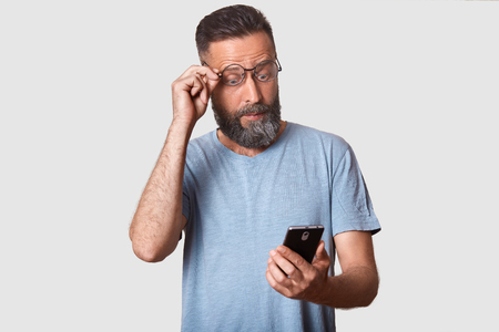 Close up studio portrait of slender bearded handsome curious man holding his smartphone in one hand, reading breaking news, watching videos at social networking sites, being deeply impressed.