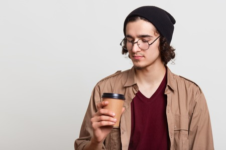 Thoughtful pensive youngster having paper cup of coffee, holding hot drink in one hand, looking attentively at it, posing isolated over light grey background in studio, being on break. Youth concept.