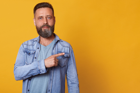 Stylish serious dark haired man looks directly at camera, standing firmly, raising one arm, showing direction aside with one forefinger, wearing casual jeans jacket and t shirt. Copyspace for ads.
