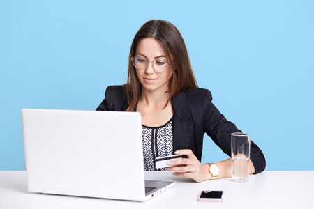 Serious successful young female sitting isolated over light blue background, holding credit card in her hand, typing numbers, entering pin code, looking attentively at laptop screen, placing order. Standard-Bild