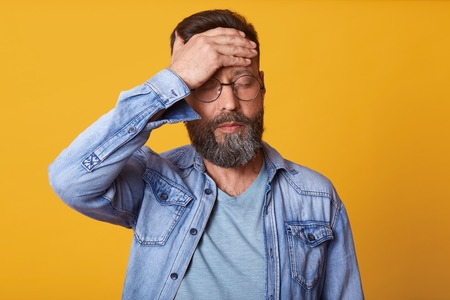 Studio shot of tensed bearded young man touches his forehead and having headache, dressed denim, gray t shirt and glasses, stands with closed eyes isolated over yellow background. Healthy care concept Stock Photo - 122682643