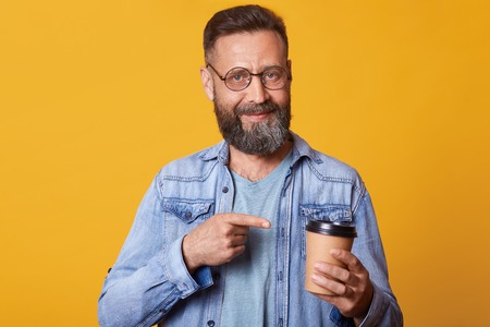 Delighted positive smiling handsome guy holding paper cup of strong coffee in one hand, pointing at it with forefinger, having lunch, enjoying rest , wearing fashionable accessories, looks satisfied.