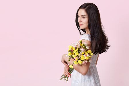Half length portrait of charming brunette woman in white sundress holding bouquet of flowers over pink background. Reklamní fotografie
