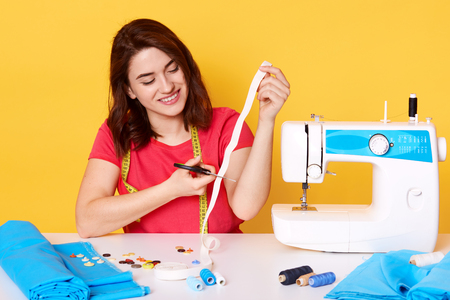 Sewer wears red casual t shirt with happy expression sitting with happy expression, cutting white ribbon, posing around sewing equipment, sews modern clothes in her workshop, isolated on yellow. Stok Fotoğraf
