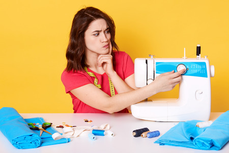 Image of thoughtful attractive brunette female, fashion designer thinks about new new sewing machine, does not know how to use it, has pensive expression, model posing isolated over yellow background. Stock Photo
