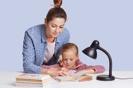 Beautiful Caucasian woman helping her daughter to do school homework, mother and child surrounded by books, little girl sitting concentrated at white desk, trying to do sums. Education concept.