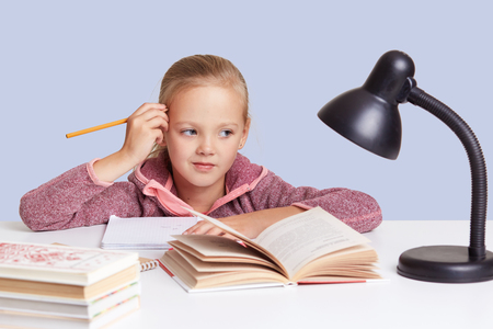 Studio shot of little schoolgirl keeps hand near head, looks with thoughtful expression directly at camera, thinks about homework task, uses reading lamp. Children, education and schooling concept.