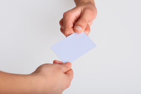 Studio shot of hand giving blank plastic card or paper flyer, isolated on white background, copy space for your advertisement or promotion text. Stock Photo