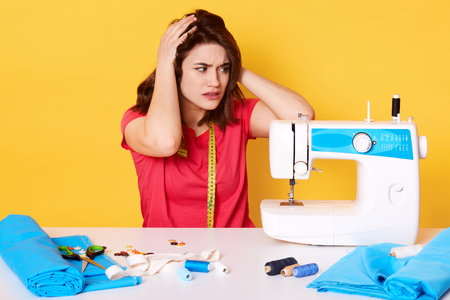 Indoor shot of seamstress sewing in studio, keeps hands on had, has broken sewing machine, wearing red t shirt, has measure tape on neck, surrounded by different sewing equipment, isolated on yellow. 写真素材