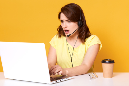Half lengh photo of nervous young woman operator sitting with opened mouth, looking at laptopon screen, isolated over yellow background in studio. Dark haired surprised model working in office.