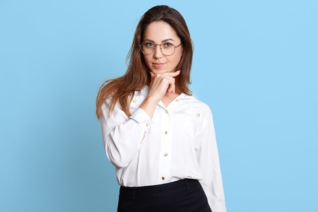 Image of beautiful slim business woman standing isolated on blue studio wall, keeps hand under chin, looks directly at camera with thougtful facial expression, has new plan for aiming her career goals Imagens