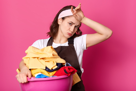Tired hard working female with frowned face touching her forehead with hand, wiping out sweat, having lots of housework, taking clean clothes out of laundry, looking directly at camera with sadness.