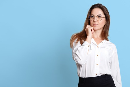 Portrait of young pensive woman touching her chin, has something in mind, posing with thoughtful facial expressions, wearing white shirt and black skirt, isolated over blue background. Copy space.