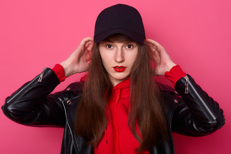 Indoor shot of young teenager wearing stylish red hoodie, leather jacket and black cap, keeps hands on head, looking directly at camera. Model posing in studio against pink wall. Teens concept.