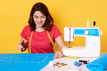 Image of brunette girl wears red t shirt, sitting isolated over yellow background, holds scissos in hand, has charming smile, sews stylish dress, sitting surrounded with different sewing equipment.