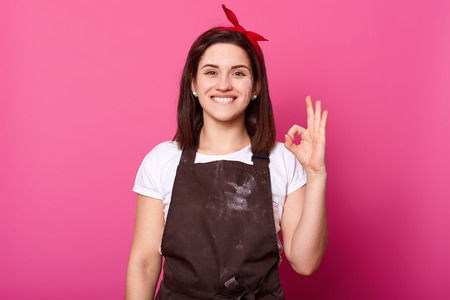 Close up portrait of beautiful young woman shows ok sign, lady with toothy smile, has happy facial expression, being in good mood, posing against pink studio wall. People feelings and emotions concept