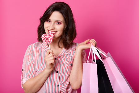 Close up portrait of attractive young girl with dark wavy hair wearing striped shirt standing with sweet lollypop in shape of heart and holding shopping bags over pink background. Shopping concept. Stockfoto