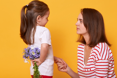 Happy mother's day! Cute child girl congratulates her mother on holiday and wants to give flowers. Daughter hides bouquet of blue florets behinds her back, mum holding her charming kid's hand.
