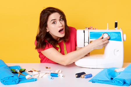 Photo of young lady works in her sewing space, has problems with sewing machine, creates accessories, repairing clothes, embroider and packs trendy clothes, sitting against yellow studio wall.