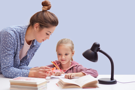 Studio shot of little charming girl sits at table, has difficult homework task, her mother trying to help daughter and explains mathematics rules, uses reading lamp for good vision. Education concept. Banco de Imagens