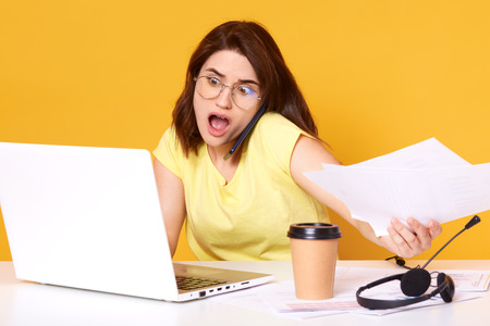 Beautiful businesswoman in eyeglasses, siting at desk, surounded with cup of coffee or tea, headset, computer, looking at lap top screen with shocked expression and opened mouth, holds papers in hand.