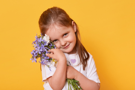 Shy but beautiful smiling girl wearing white casual t shirt standing isolated over bright yellow studio background, wants to congratulate her mother with holiday. Happy Mothers Day! Children concept.