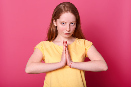 Close up portrait of serious beautiful Caucasian female posing in studio, looks directly at camera with confident expression, keeps hands in praying gesture, wearing yellow t shirt, isolated over pink.