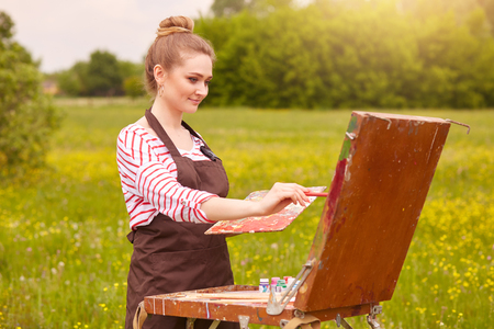 Outdoor shot of young girl artist paints picture in open air. Painting lesson in nature. Attractive blonde wears casually, paints landscape in spring meadow. Brush on canvas, creating and art concept. Banco de Imagens