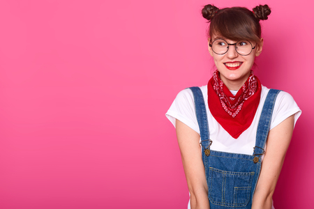 Young smiling sweet girl looking aside, wearing casual white t shirt, jeans overalls, red bandanna and round trendy spectacles, being in high spirits, having bunches. Copy space for advertisement.
