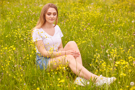 Close up portrait of young model blonde woman sitting on grass, posing in white casual t shirt and denim skirt, has romantic expression, siting on ground surrounded field flowers and looking down.