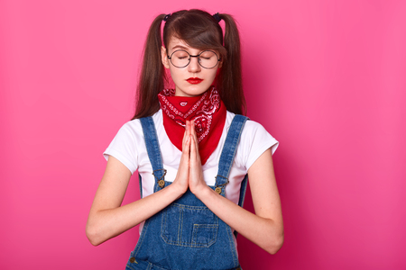 Close up portrait of calm beautiful Caucasian female teenager with ponytails, keeps eyes closed, prays while standing against pink wall, wears white t shirt, overalls, red bandanna on neck and glasses.