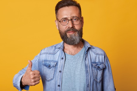 Pleased and good looking male in sunglasses, denim jacket and gray t shirt, raising thumb up and looking at camera, giving positive feedback, standing over yellow studio wall. Body language concept. Stock Photo