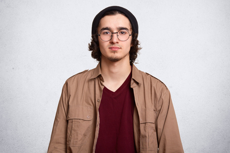 Close up portrait of serious man with curly hair, wearing maroon shirt, brown jacket, black cap and rounded spectacles, looking directly at camera, model posing isolated over white studio background. 版權商用圖片